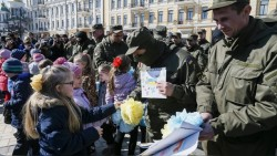 """Children present their paintings to servicemen of the Ukrainian national guard battalion """"Donbass"""" before they depart to the frontlines in eastern Ukraine, in central Kiev"""